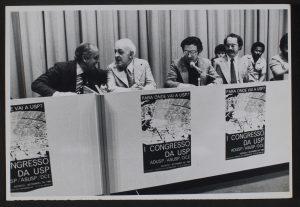 Foto preto e branco com a mesa de debates e 4 homens maduros de terno e gravata sentados. Em frente a mesa figura 3 cartazes iguais onde se lê: I Congresso da USP. Ao fundo da mesa 3 homens mais jovens sentados de camisa.