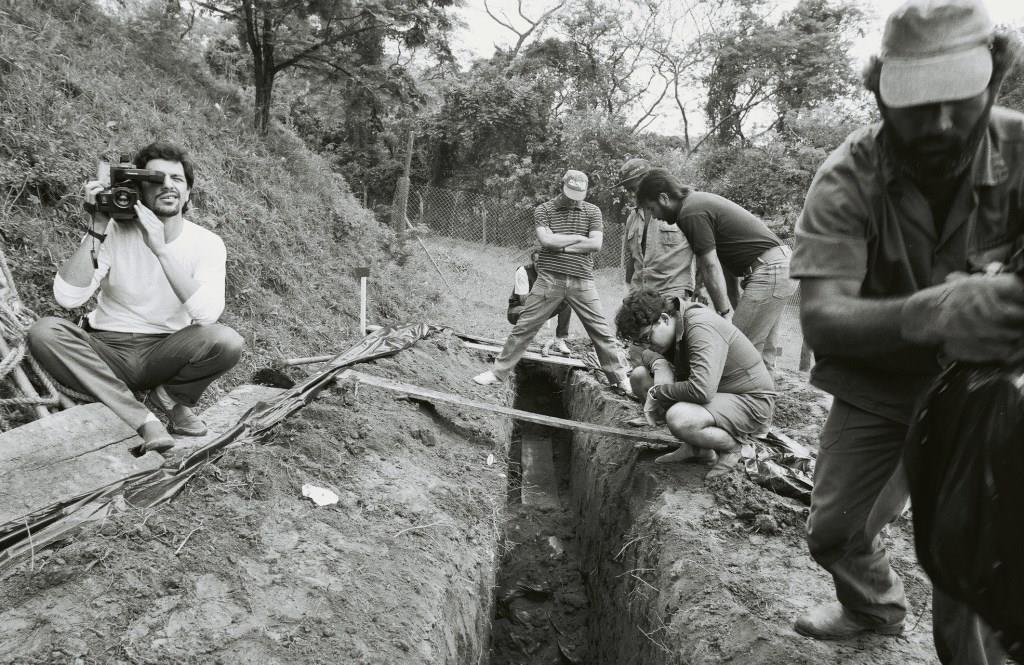 Foto em preto e branco de quatro homens observando uma vala. No canto direito um homem carrega um saco preto e no canto esquerdo um cinegrafista filma de cócoras.