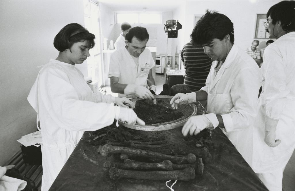 Foto em preto e branco de dois homens e uma mulher vestidos de branco e luvas manipulando ossos que estão sobre uma mesa. Eles usam uma peneira para separar a terra dos ossos. Na lateral direita hum homem de branco passa.