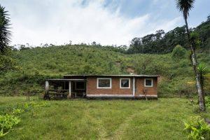 Foto colorida de casa térrea atrás de um gramado verde. A construção tem 3 janelas quadradas com soleira branca e é de tijolos a vista. No canto esquerdo da casa uma pequena varanda. O telhado da construção é de telhas onduladas de amianto. Nos fundos da casa uma colina com grama verde.