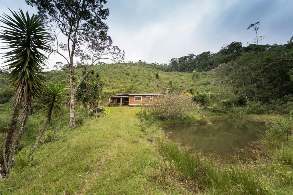Foto colorida de casa térrea atrás de um gramado verde. NO lado deito do gramado vemos um pequeno lago A construção é de tijolos a vista. No canto esquerdo da casa uma pequena varanda. O telhado da construção é de telhas onduladas de amianto. Nos fundos da casa uma colina com grama verde.