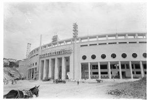Foto em preto e branco de um estádio de futebol pelo lato de fora. Sua fachada é circular, e a entrada tem colunas muito altas. A parte da frente da fachada vemos uma área de terra batida. No canto inferior esquerdo da foto vemos um burrinho com sela.
