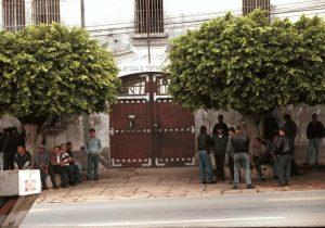 Foto colorida de pessoas paradas ao lado de um portão fechado. Elas esperam na sombra de 2 árvores (que vemos ao lado do portão) Acima dele conseguimos ler, entre as folhas das árvores as palavras: Institutos, custódia e tratamento