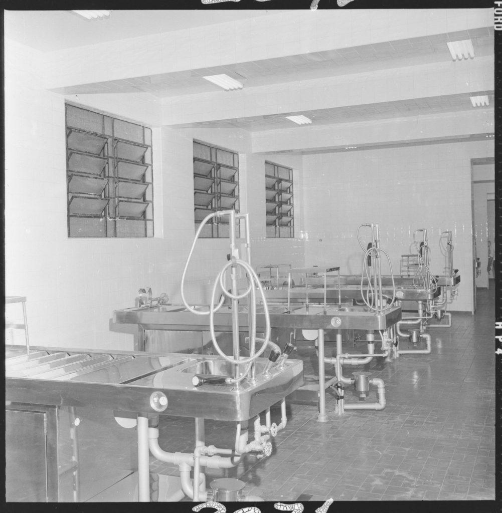 Foto em preto e branco de 4 mesas de metal com equipamentos médicos. Na ponta de cada mesa há uma pia, torneira e instalação hidráulica. O piso do espaço é de azulejo.