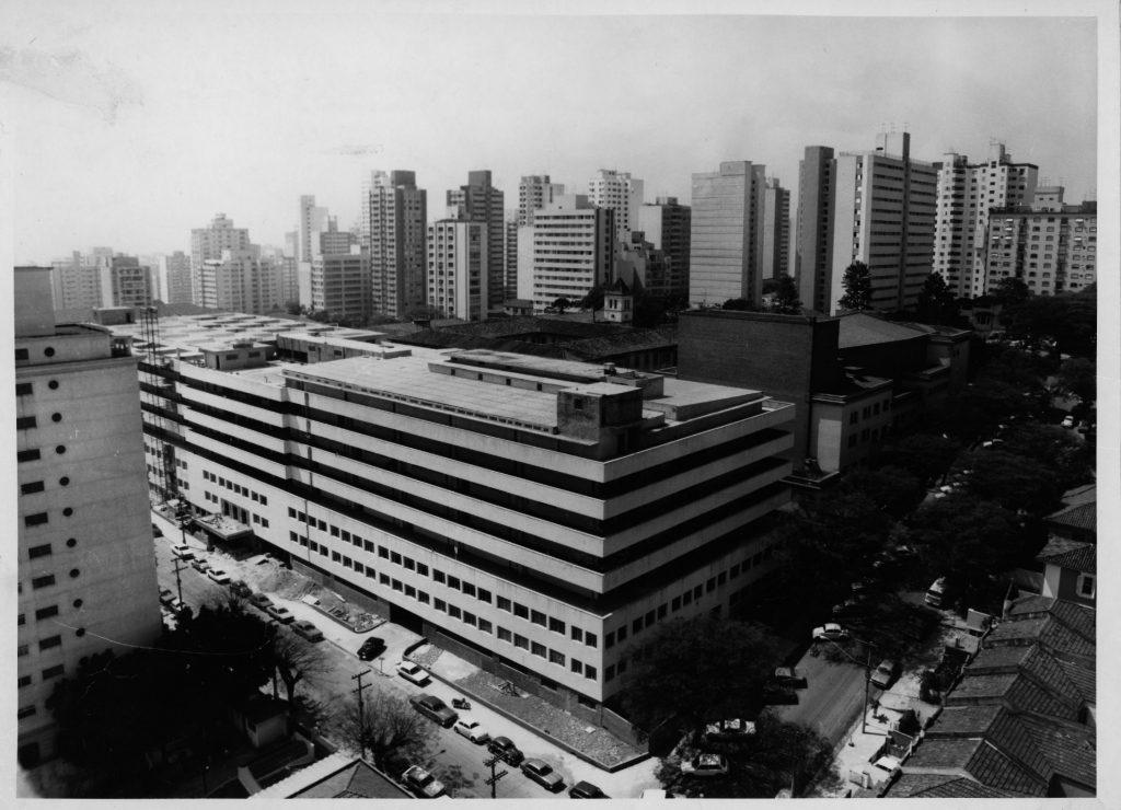 Foto em preto e branco de prédio com os dois primeiros andares com várias janelas e os 5 últimos com grandes vãos. No fundo vemos vários edifícios residenciais.