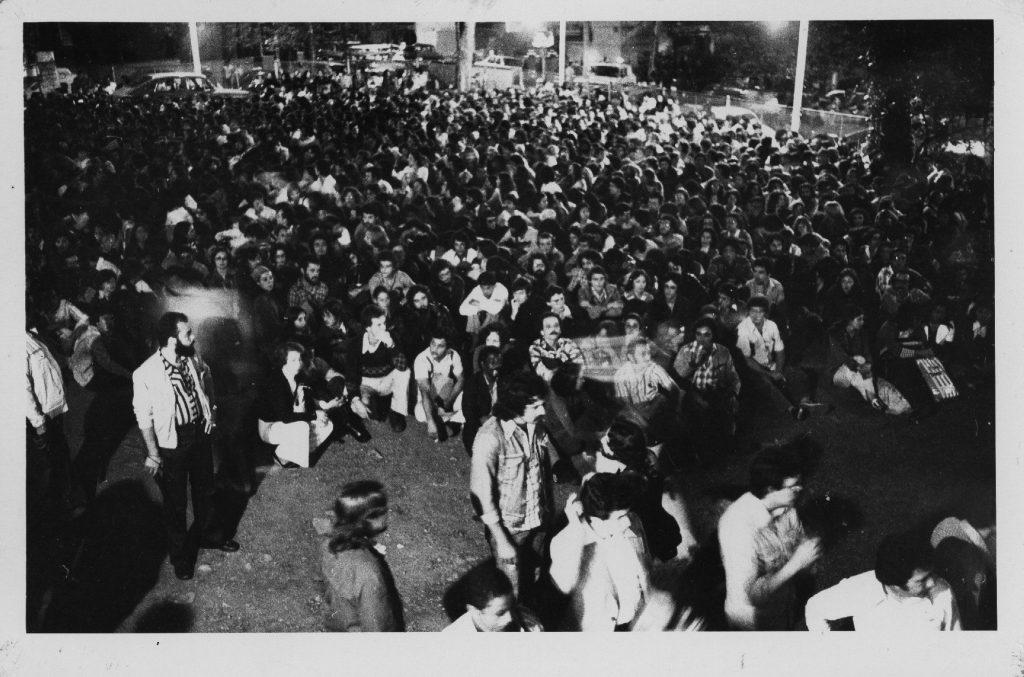 Foto em preto e branco de várias pessoas sentadas no chão de um vão e algumas pessoas em pé no primeiro plano da imagem