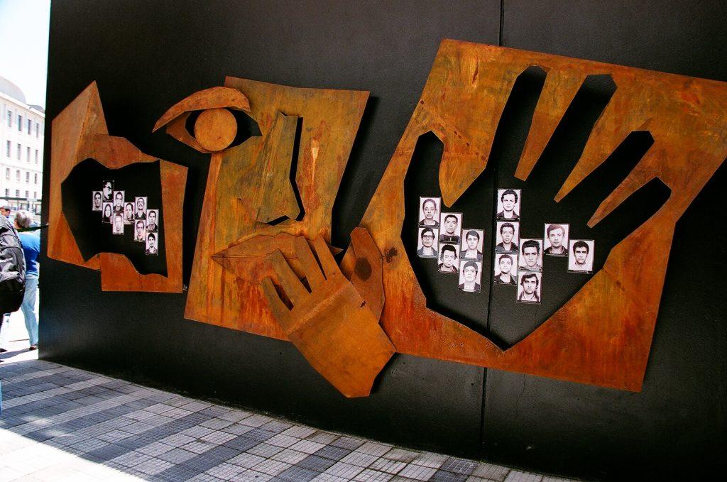 Foto colorida de instalação artística feita em ferro da cor ferrugem com a representação estilizada de um rosto e 2 mãos. Por dentro de uma das mãos, vemos 14 fotos 3x4 de jovens.