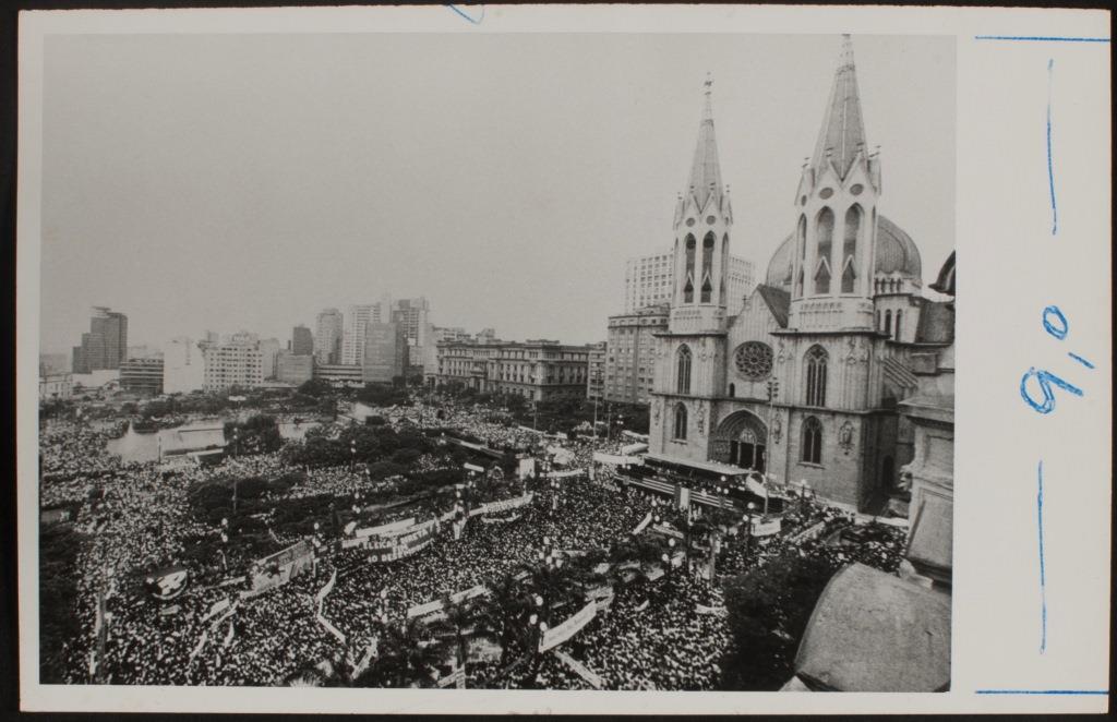 Fotografia em preto e branco de uma grande multidão aglomerada em frente a Catedral da Sé em São Paulo. A fotografia foi tirada do alto e podemos ver toda a área está repleta de pessoas, sendo que muitas delas seguram faixas. Ao fundo da imagem vemos prédios. A Igreja ocupa a lateral direita da foto e tem 2 torres de 92 metros de altura cada com janelas de arco ogival. Acima da porta de entrada, também em arco ogival, há uma rosácea (um vitral redondo). No local da escadaria em frente a igreja está montado um palanque feito em metal.