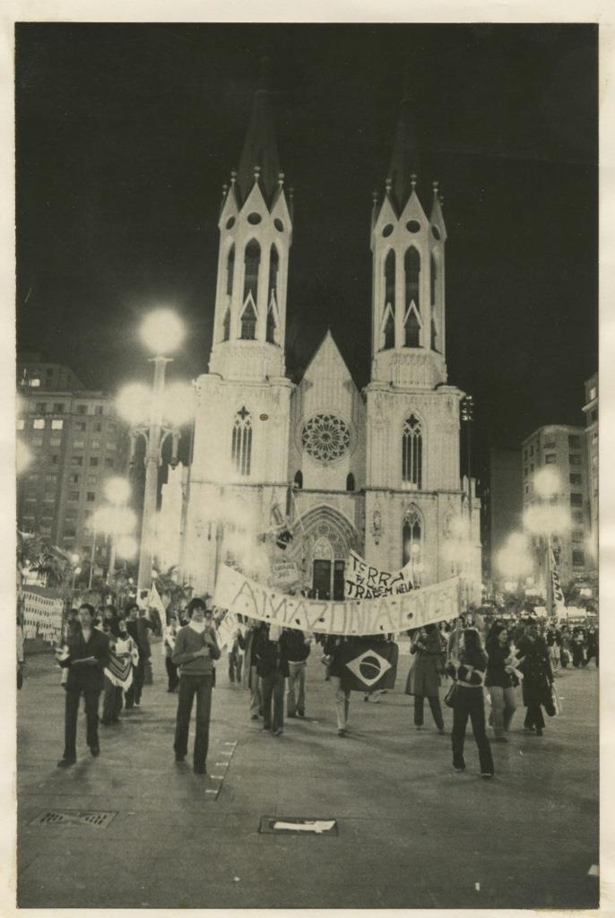 """Foto em preto e branco de grupo de pessoas em frente a uma igreja. Eles seguram uma faixa onde lê-se """"Amazonia é nossa"""" e uma bandeira do Brasil. Atrás deste grupo vemos a igreja que tem 2 torres laterais altas e uma parte central um pouco mais baixa com uma rosácea no pavimento superior e um portal com arco ogival para a entrada. As janelas ans torres laterais também são em arco ogival."""