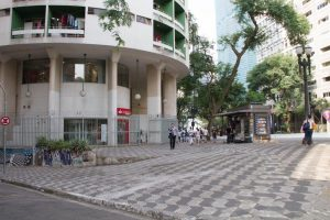 Foto colorida de espaço térreo de prédio branco,circular onde podemos ver 4 colunas retangulares. A frente do prédio um calçadão com desenhos da forma que possui o Estado de São Paulo formando um mosaico preto e branco.