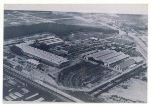 Fotografia aérea em preto e branco um pouco apagada pelo tempo. Retrata cinco galpões grandes, a sede administrativa da fábrica e um pátio para trens, árvores ao fundo do terreno e as ruas e estradas de acesso ao local.