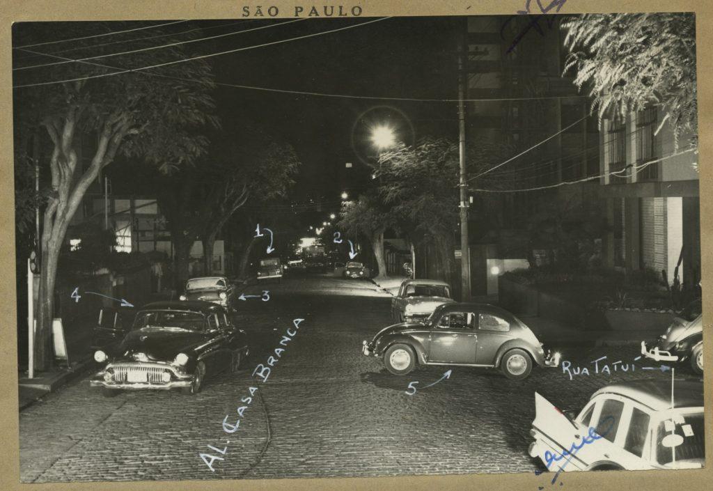Foto preta e branca de rua de paralelepípedos e largura para 3 carros. Há árvores em sua extensão e carros estacionados nas guias. Podemos identificar dois: um fusca estacionado na transversal na lateral direita e um Cadillac estacionado na lateral esquerda.