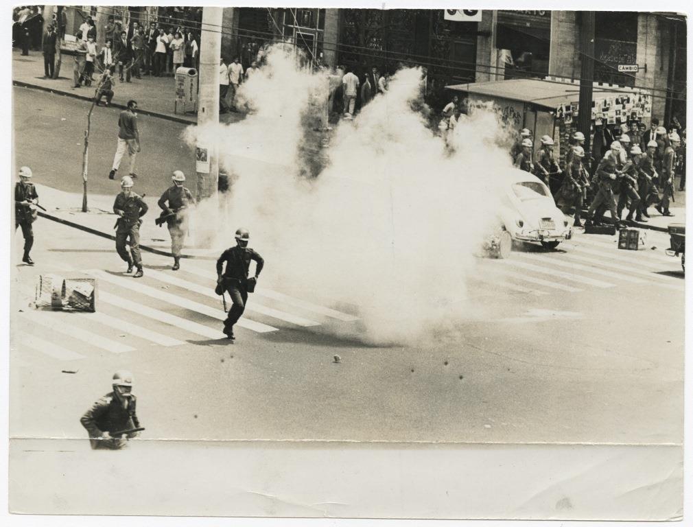 Foto em preto e branco de rua com 5 soldados armados, 3 deles em posição de ataque e 2 correndo. No meio da rua vemos uma nuvem de fumaça. Atrás da nuvem, vemos um fusca passando. A calçada, pessoas afastadas observam. Na esquina, próximo ao fusca, um batalhão de soldados marcha.