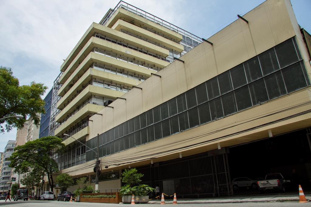 Foto colorida de prédio de 12 andares na lateral esquerda com um anexo de 5 andares na lateral direita. Ele é na cor bege na parte de concreto, com janelas de vidros escuros. A parte anexa tem uma grande entrada para carros.