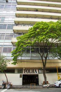"""Foto colorida de entrada de pedestres de um prédio com muitas janelas de vidro. Sobre a porta de entrada lemos cm letras grandes a palavras """"Folha"""" com a mesma tipografia utilizada na logomarca da Folha de São Paulo."""