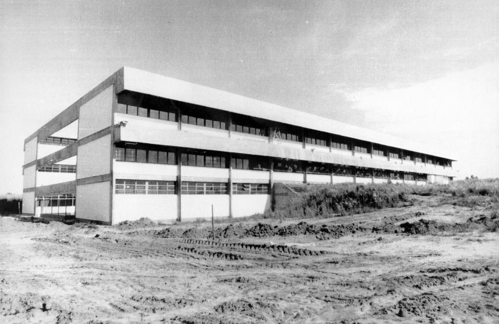 Foto em preto e branco de um grande prédio de 3 pavimentos em construção. A fachada é branca com janelas seguidas. À frente dele há o terreno mexido de terra com marcas de trator