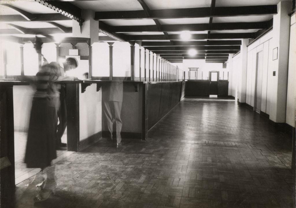 Foto em preto e branco de um corredor amplo e largo com piso de taco. Há um enorme balcão vazio que ocupa quase toda a área. No canto esquerdo uma mulher de saia até debaixo do joelho com as mãos sobre o balcão aguarda, enqtanto um homem um homem olha para baixo.