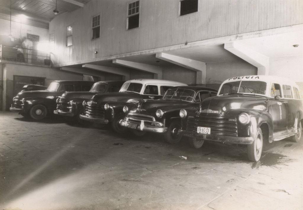 """Fotografia em preto e branco de um estacionamento coberto com 5 carros dos anos 50. Todos são escuros sendo que 2 deles (o do canto direito e o do centro) são viaturas, pois tem a cobertura branca e tem o escrito """"polícia"""" na junção entre o para-brisa e a cobertura."""