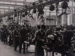 Foto em preto e branco de vários homens uniformizados trabalhando na construção de motores de carros entre muitas máquinas. Para cada motor, 2 homens trabalham. O chão é de cimento e o teto parece ter uma clarabóia que permite a entrada de luz solar.